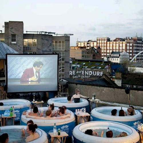 Picture of hot tubs on a roof in front of a screen playing a film